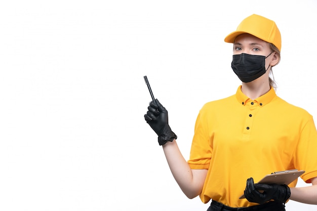 A front view young female courier in yellow uniform black gloves and black mask holding notepad and pen