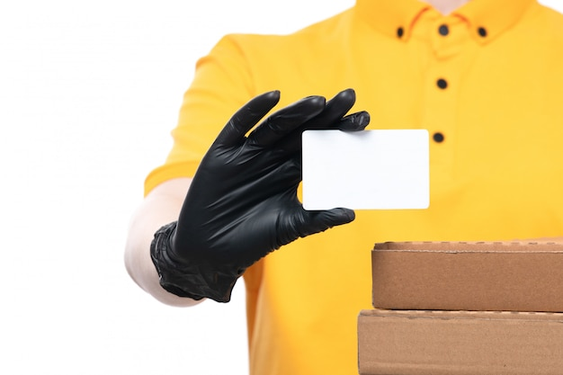 A front view young female courier in yellow uniform black gloves and black mask holding pizza boxes and holding white card
