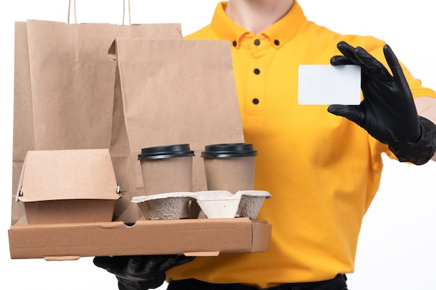 A front view young female courier in yellow uniform black gloves and black mask holding pizza boxes and white card delivering