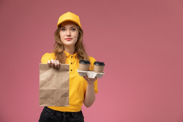 Front view young female courier in yellow uniform holding coffee cups and food package on dark pink desk uniform delivery job service worker