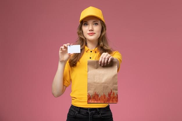 Vista frontale giovane corriere femminile in uniforme gialla che tiene il pacchetto di cibo di consegna e carta di plastica sul lavoratore femminile uniforme di servizio di consegna sfondo rosa