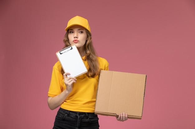 Giovane corriere femminile di vista frontale in blocco note giallo della tenuta uniforme e pacchetto di consegna del cibo su sfondo rosa lavoratore di servizio colore consegna uniforme di lavoro
