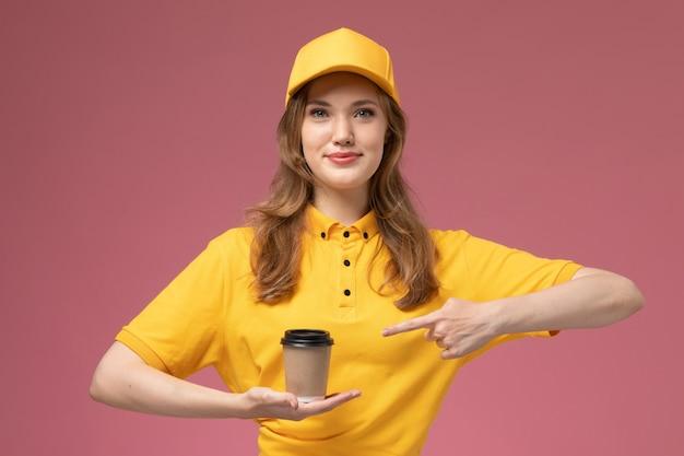 Giovane corriere femminile di vista frontale in uniforme gialla che tiene la tazza di caffè di plastica marrone sulla lavoratrice di servizio di consegna uniforme scrivania rosa scuro