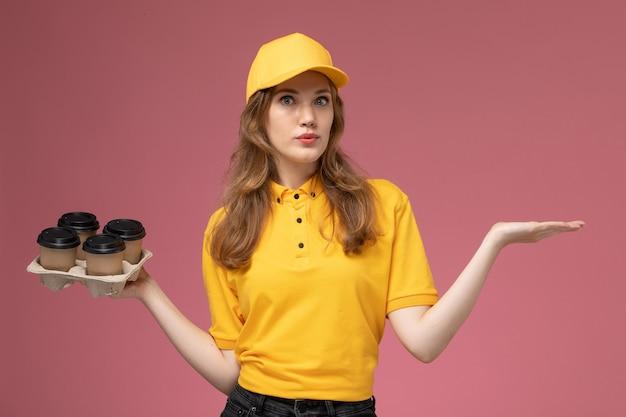 Giovane corriere femminile di vista frontale in uniforme gialla che tiene le tazze di caffè marroni di plastica sul lavoratore di servizio di colore di consegna uniforme di lavoro di sfondo rosa