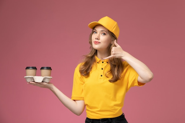 Front view young female courier in yellow uniform holding plastic brown coffee cups posing on pink background job uniform delivery color service worker