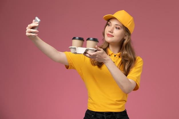 Giovane corriere femminile di vista frontale in uniforme gialla che tiene le tazze di caffè marroni di plastica che prendono selfie con loro sul lavoratore di servizio colore consegna uniforme di lavoro sfondo rosa