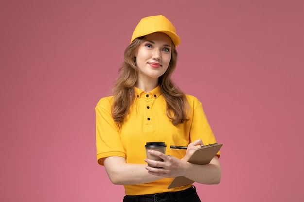 Front view young female courier in yellow uniform holding plastic coffee cup smiling on the dark-pink background uniform delivery job service worker