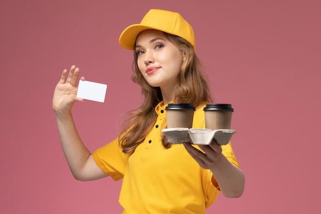 Front view young female courier in yellow uniform holding plastic coffee cups and white card on dark pink desk uniform delivery service worker