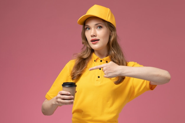 Front view young female courier in yellow uniform yellow cape holding coffee cup on the dark-pink background uniform delivery service female worker