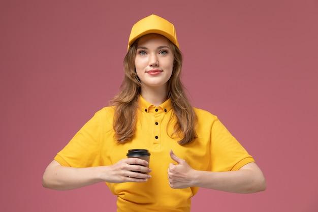 Corriere femminile giovane vista frontale in mantello giallo uniforme giallo che tiene la tazza di caffè con un leggero sorriso sul lavoratore di sesso femminile di servizio di consegna uniforme sfondo rosa scuro
