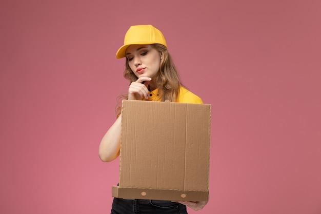 Giovane corriere femminile di vista frontale in mantello giallo uniforme giallo che tiene la scatola di consegna del cibo sul colore di servizio di lavoro di consegna uniforme da scrivania rosa scuro