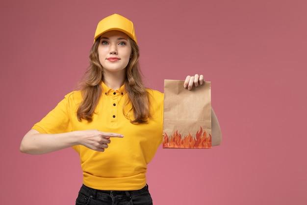 Corriere femminile giovane vista frontale in capo giallo uniforme giallo che tiene il pacchetto di consegna del cibo su colore di servizio di lavoro di consegna uniforme sfondo rosa