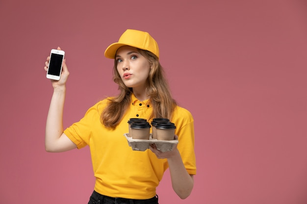 Front view young female courier in yellow uniform yellow cape holding phone and plastic coffee cups on the dark-pink background uniform delivery job service color