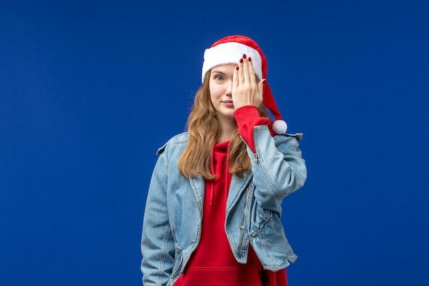 Giovane femmina di vista frontale che copre metà del suo viso su sfondo blu colore di emozione di natale