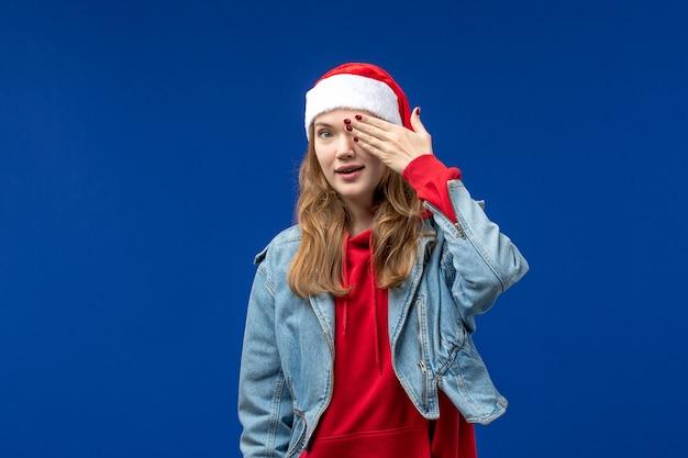 파란색 배경 크리스마스 감정 색상에 그녀의 얼굴의 절반을 덮고 전면보기 젊은 여성