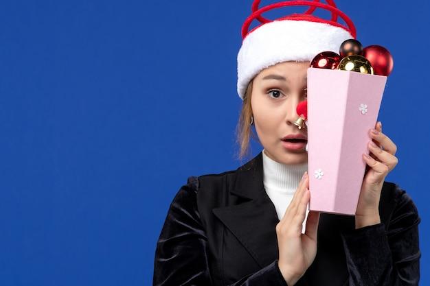 Giovane femmina di vista frontale che copre il viso con i giocattoli sulla vacanza di capodanno emozione parete blu