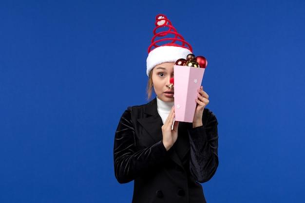 Вид спереди молодая женщина закрыла лицо игрушками на синей стене эмоции новогоднего праздника