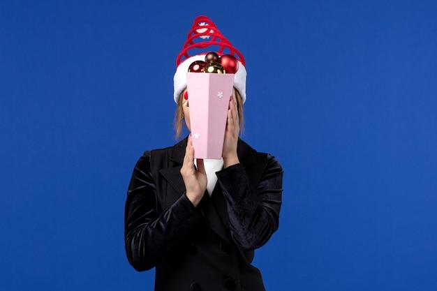 Вид спереди молодая женщина закрыла лицо игрушками на синей стене эмоции новогодних праздников