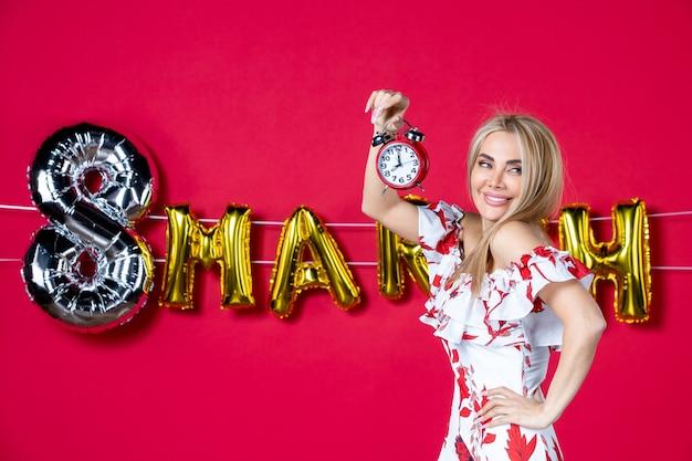Vista frontale giovane donna in abito carino che tiene l'orologio sul tempo di colore rosso