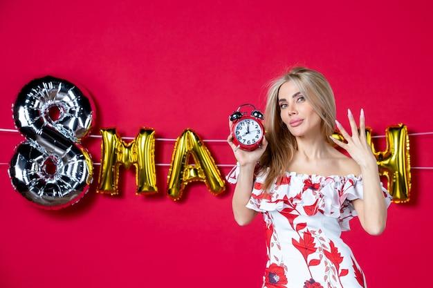 Vista frontale giovane donna in abito carino che tiene l'orologio sul colore dell'ora rossa