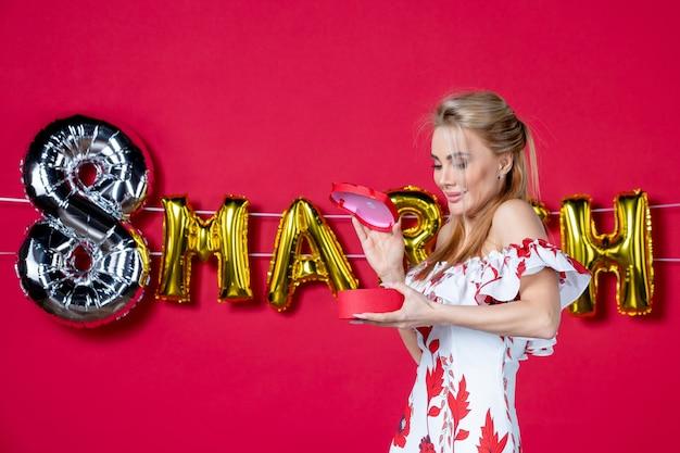 Vista frontale giovane donna in abito carino che tiene e apre il presente sul colore del giorno delle donne di bellezza rosso decorato