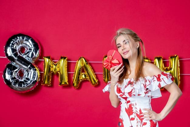 Vista frontale giovane donna in abito carino che tiene presente sul rosso decorato