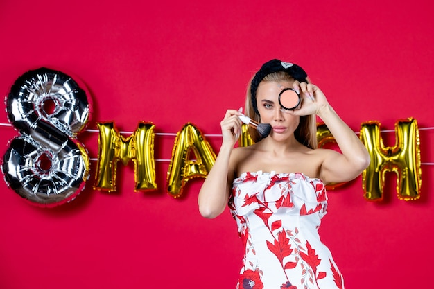 Vista frontale giovane donna in abito carino che tiene nappa e polvere per il modello di labbra rosse