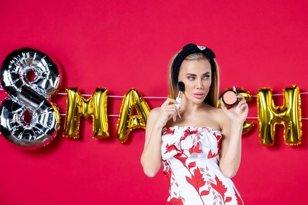 Vista frontale giovane donna in abito carino che tiene nappa e polvere per la foto in tempo rosso