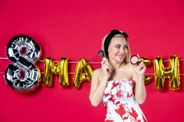 Vista frontale giovane donna in abito carino che si prepara a fare sul salone rosso