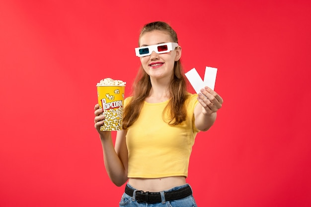 Front view young female in d sunglasses at cinema holding tickets and popcorn on red wall movie theater cinema female color