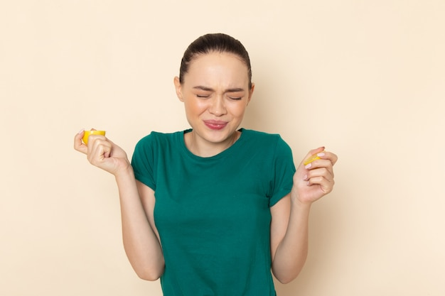Front view young female in dark green shirt and blue jeans biting lemon on beige