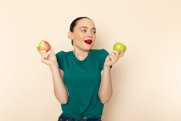 Front view young female in dark green shirt and blue jeans holding apple and pear on beige
