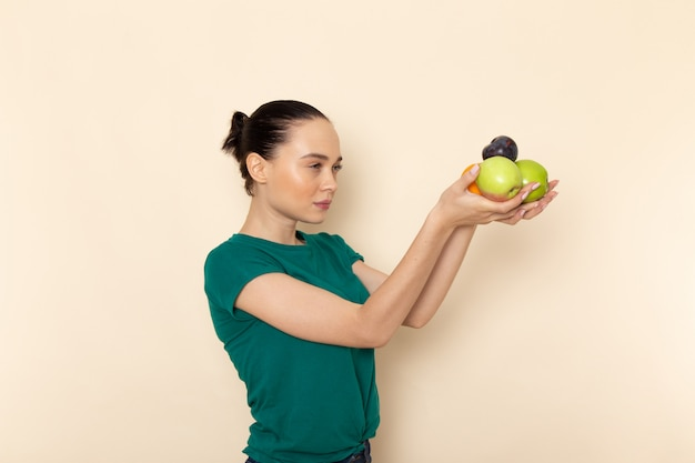 Front view young female in dark green shirt and blue jeans holding apples and oranges on beige