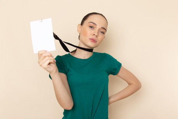 Front view young female in dark green shirt and blue jeans holding card on beige