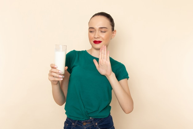 Front view young female in dark green shirt and blue jeans holding glass of milk refusing to drink on beige