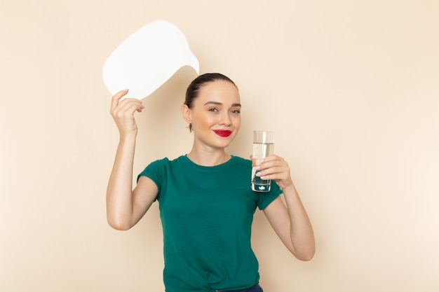 Front view young female in dark green shirt and blue jeans holding glass of water and white sign on beige