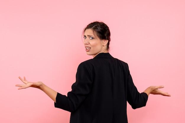Vista frontale giovane femmina in giacca scura su sfondo rosa