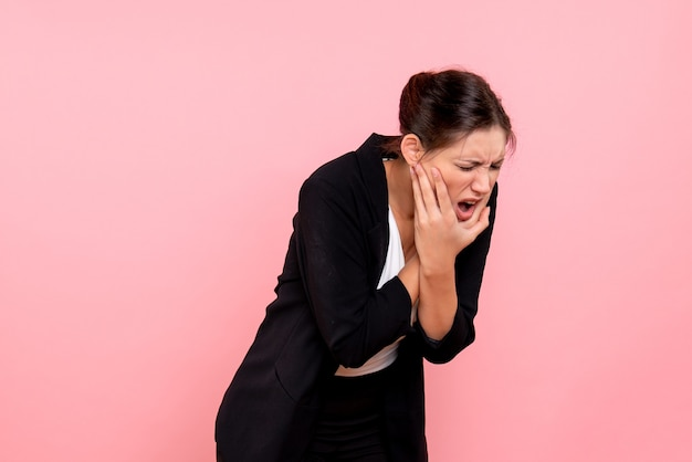 Front view young female in dark jacket suffering from toothache on pink background