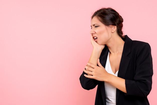 Vista frontale giovane femmina in giacca scura soffre di mal di denti su sfondo rosa