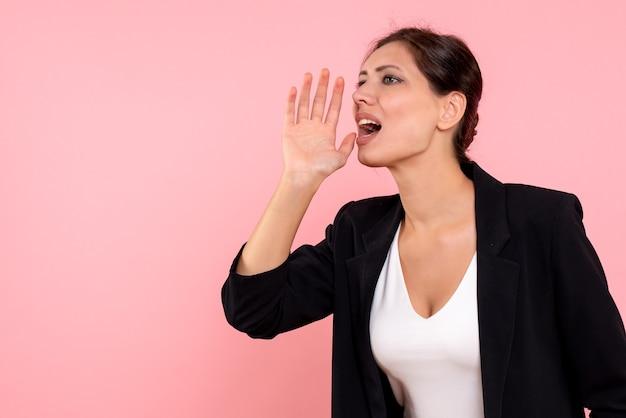 Giovane femmina di vista frontale in giacca scura e camicia bianca che chiama su sfondo rosa