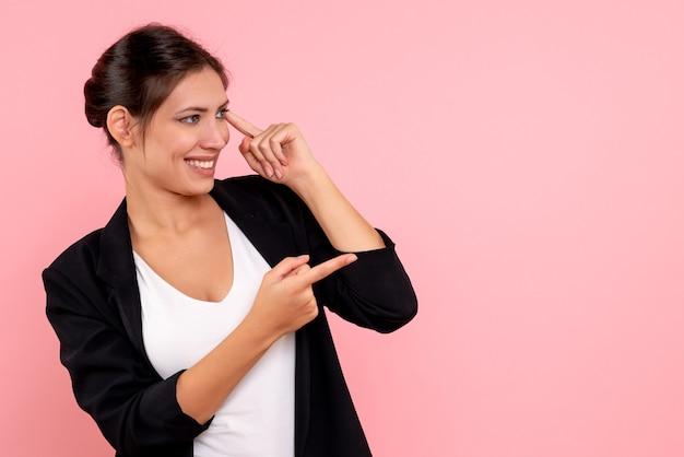 Giovane femmina di vista frontale in giacca scura e camicia bianca su sfondo rosa