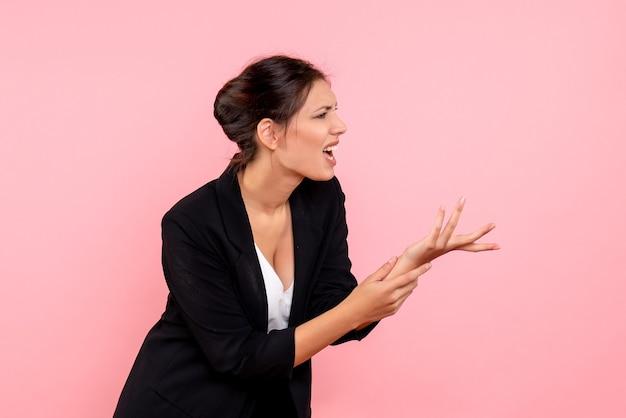 Vista frontale giovane femmina in giacca scura con mano ferita su sfondo rosa