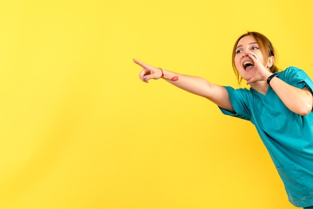 Vista frontale del giovane medico femminile che chiama sulla parete gialla