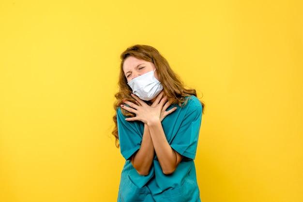 Вид спереди молодая женщина-врач с проблемами дыхания на желтом пространстве