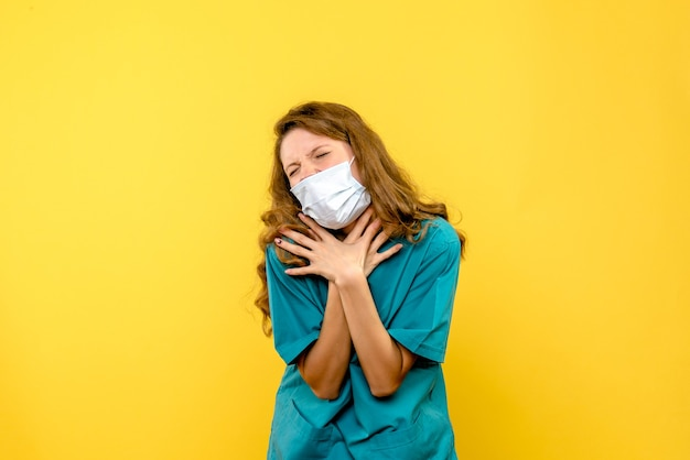Front view young female doctor having breath problems on yellow space