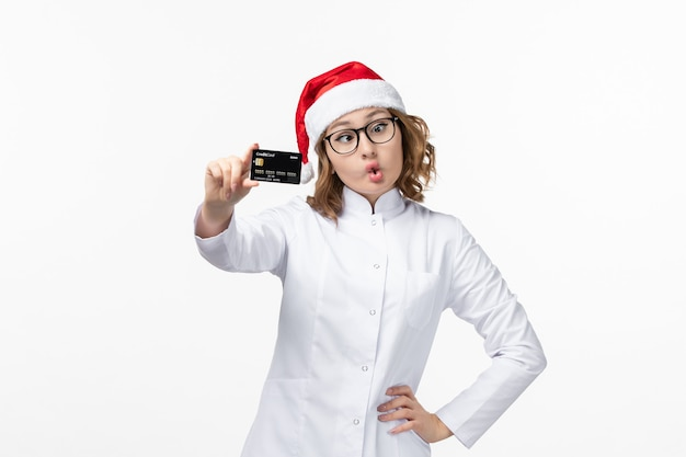 Front view young female doctor holding bank card on white floor holiday nurse new year