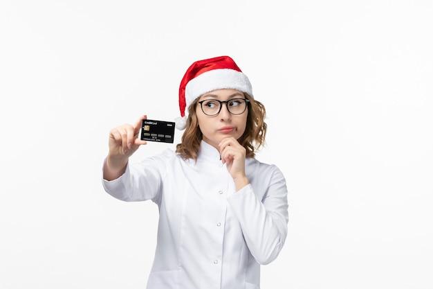 Vista frontale giovane medico femminile che tiene la carta di credito sul pavimento bianco infermiera soldi nuovo anno