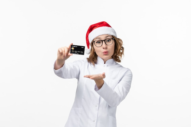 Front view young female doctor holding bank card on white wall holidays nurse new year