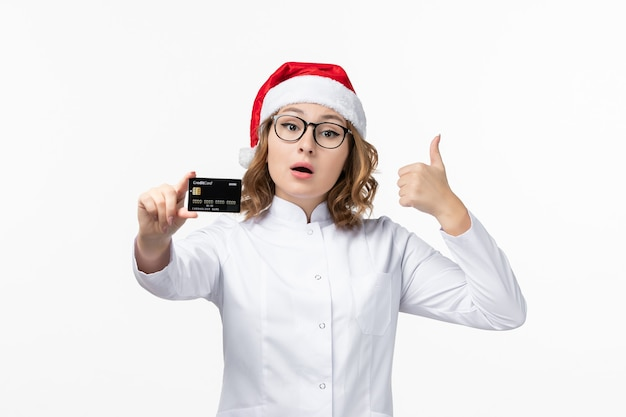 Front view young female doctor holding bank card on the white wall money nurse new year