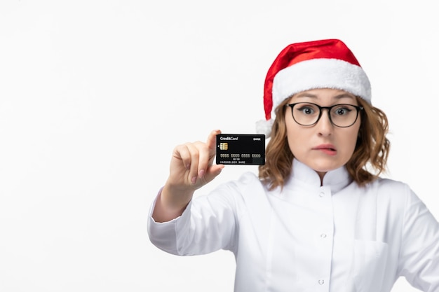 Front view young female doctor holding bank card on white wall money nurse new year